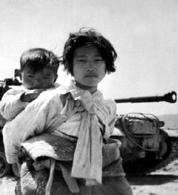 Korean children in front of a tank
